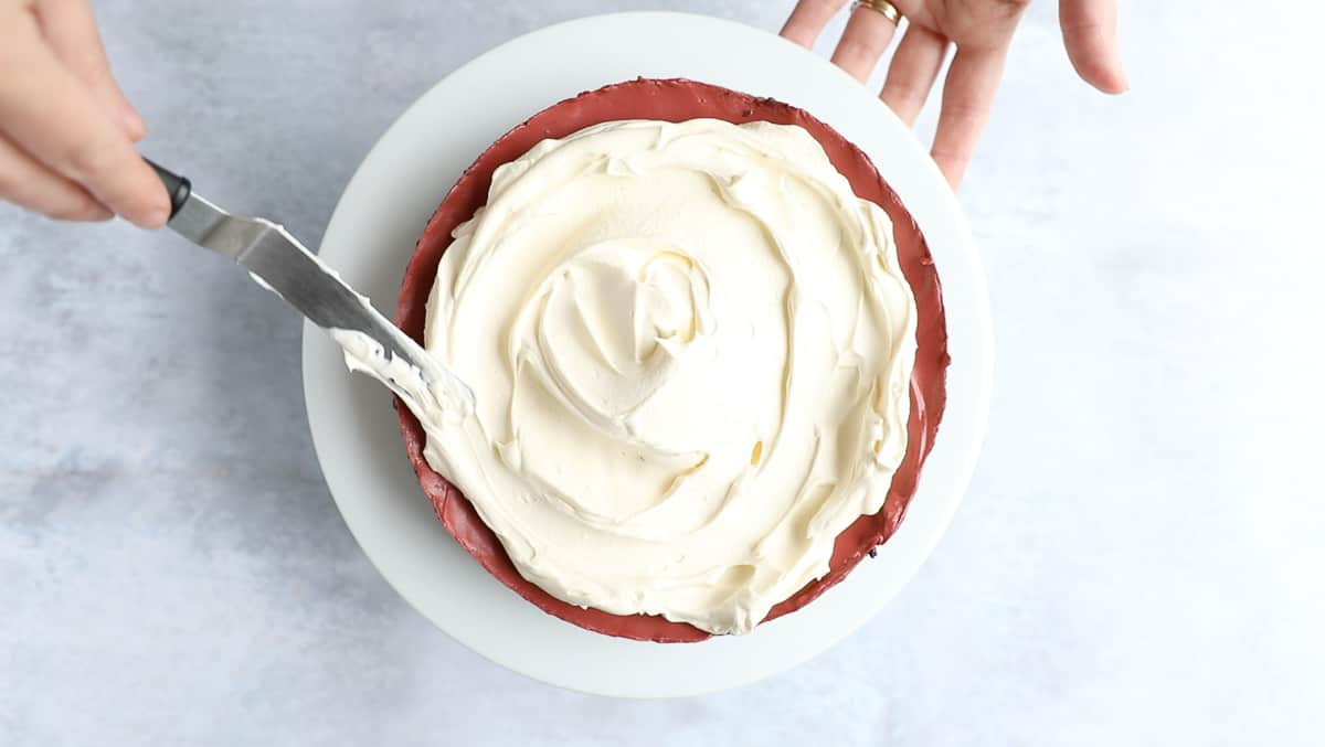 Using an off set spatula to spread whipped cream on top of cheesecake filling.
