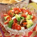 a bowl of pico de gallo with chopped avocados on top surrounded by a red and yellow tablecloth.
