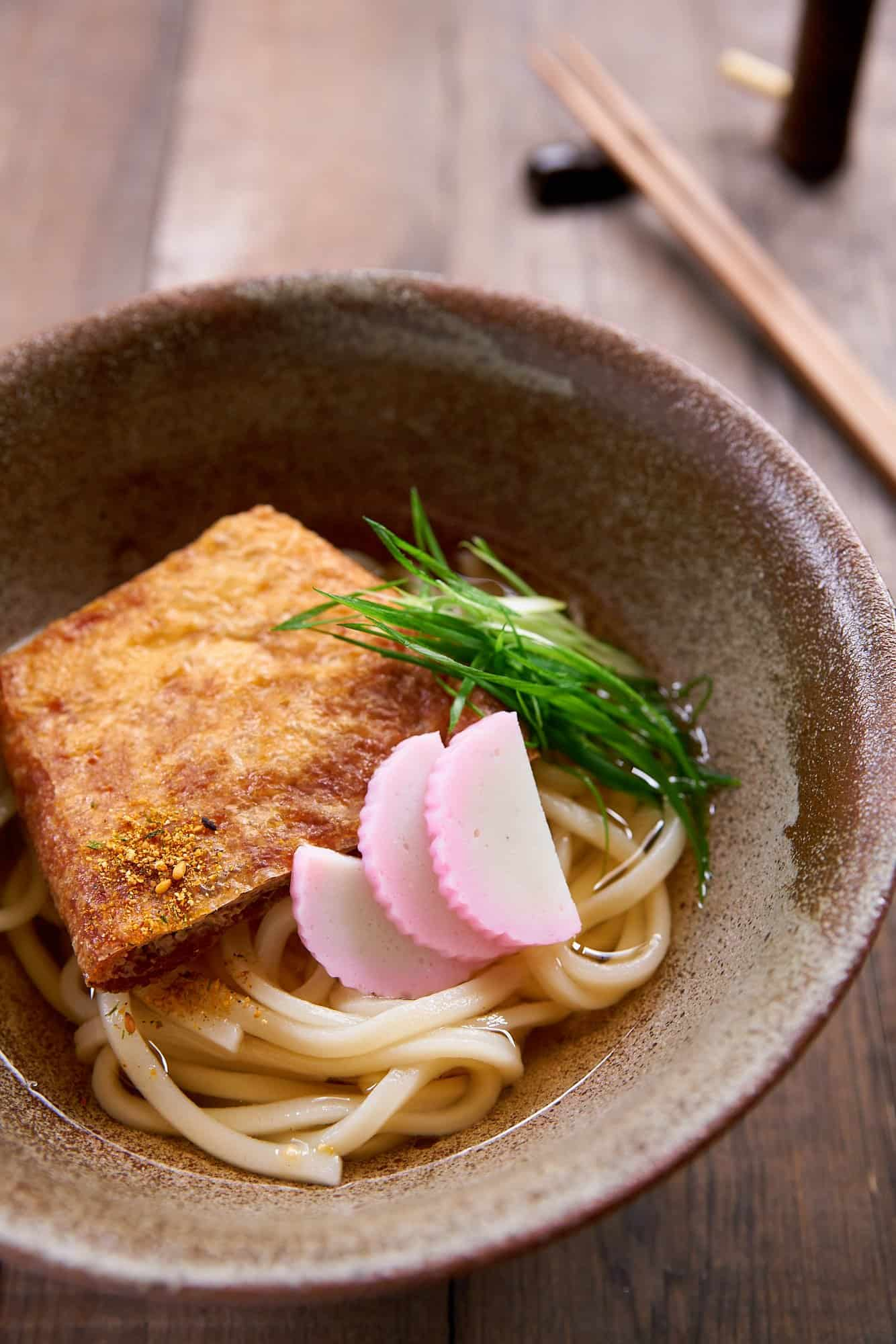 A classic Japanese noodle soup, Kitsune Udon features thick udon noodles in a light dashi broth, with a savory sweet slice of fried tofu on top.
