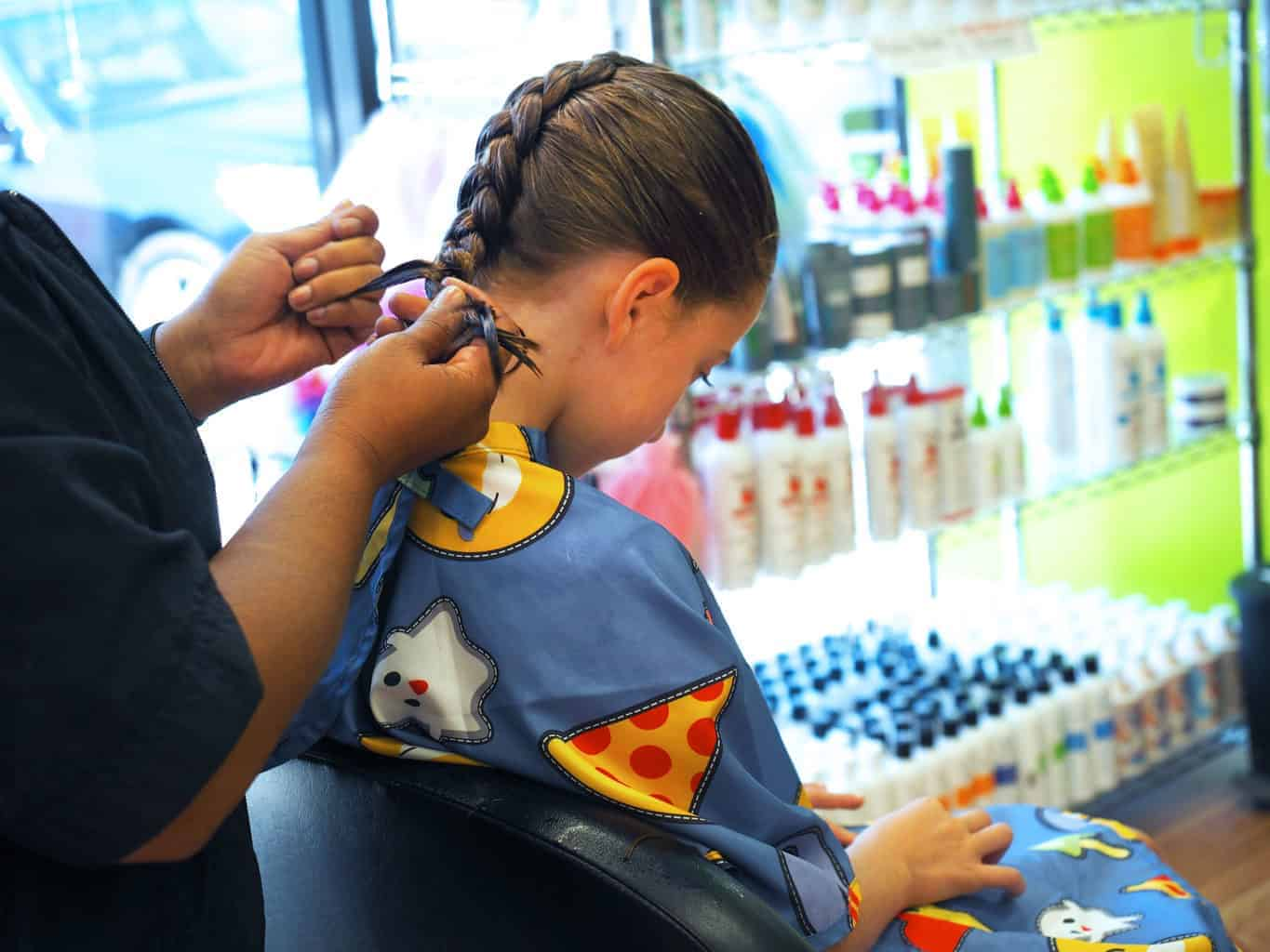 girl getting her hair braided in pigtails and crewcuts kids haircut franchise
