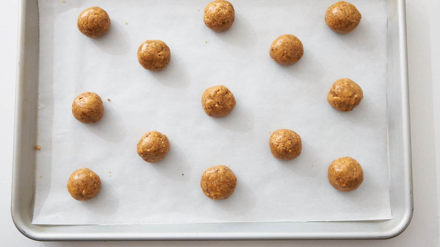 Peanut butter cookie dough rolled out into balls on a sheet pan.