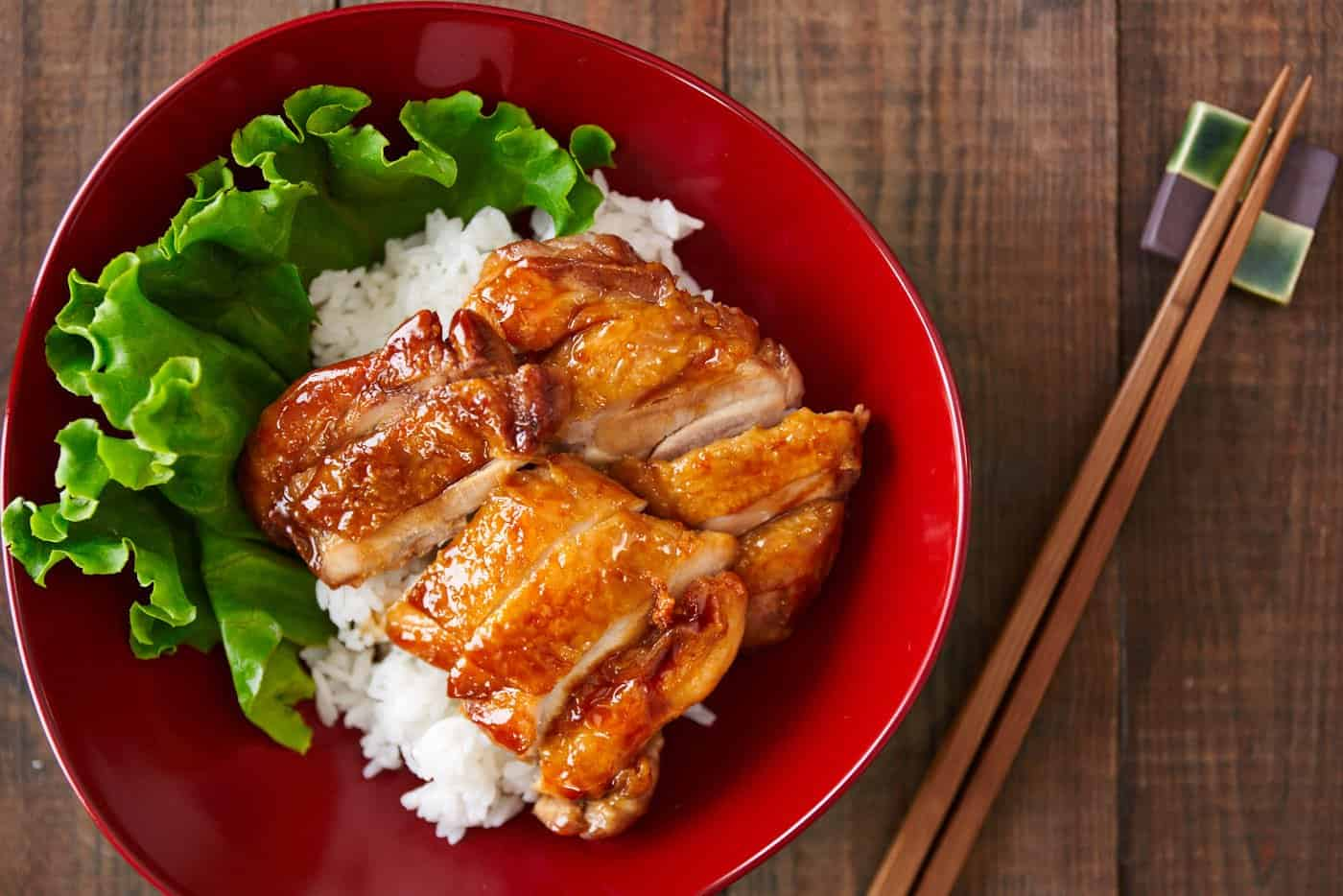 Delicious savory sweet Chicken Teriyaki in a red bowl over rice. Lean to make this easy Japanese favorite.