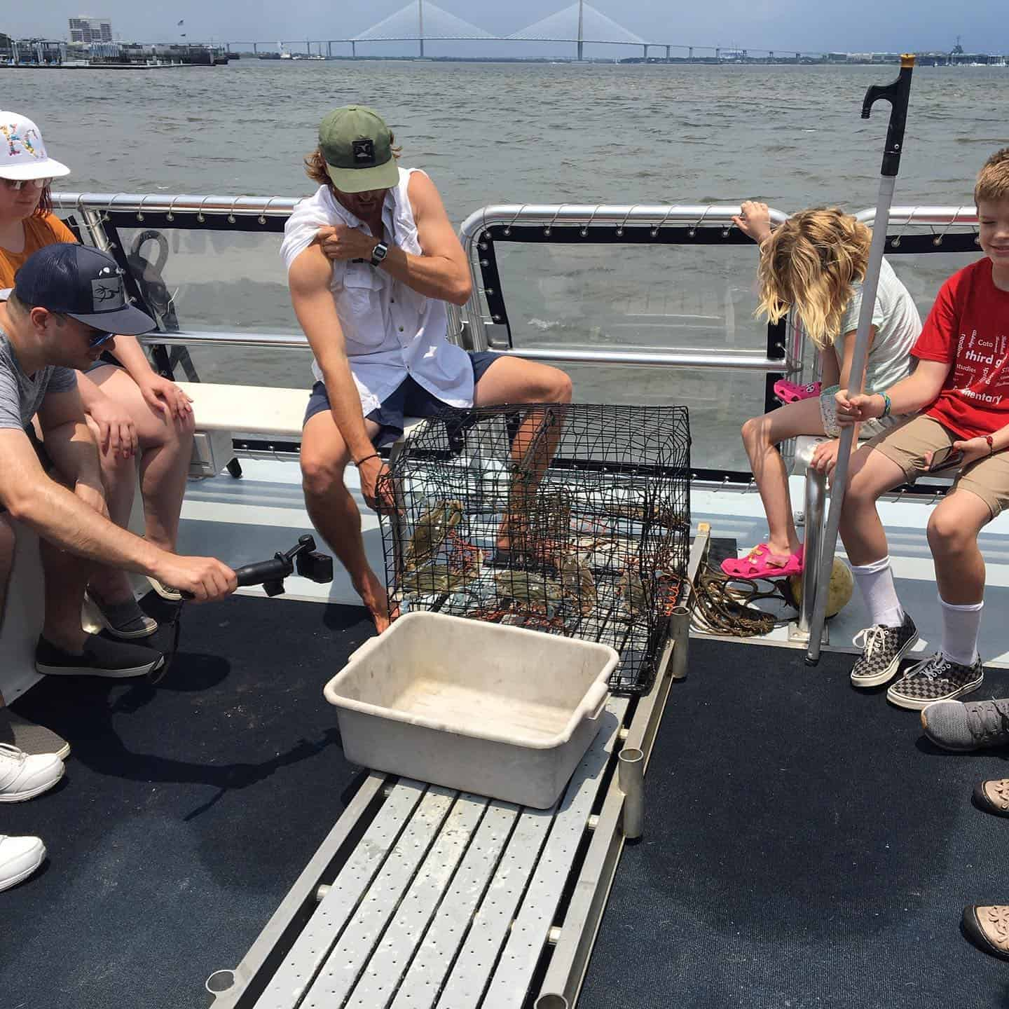 Children and adults admiring crabs caught in crab trap. Nature boat tours Charleston