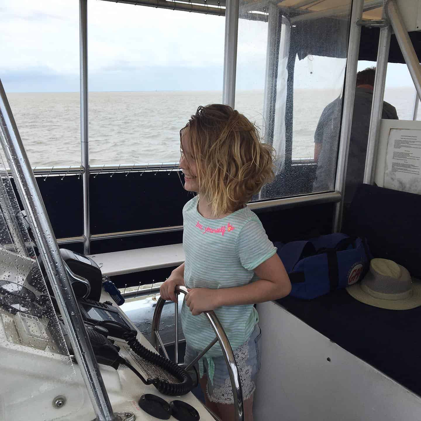 Kid happily driving the boat. Best boat tours in Charleston, SC