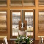 plantation shutters from medium hardwood material on white French doors
