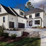 a white transitional house with black roof