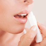 Woman applying homemade lip balm on her lips