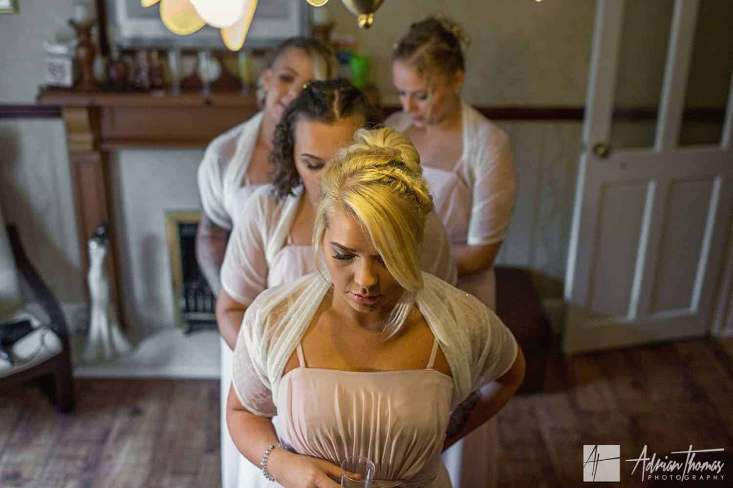 Four bridesmaids tieing each other's dress bows.