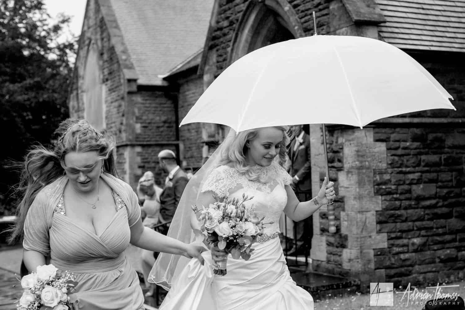 Bride with umbrella outside St Martin's Church Caerphilly wedding in rain.