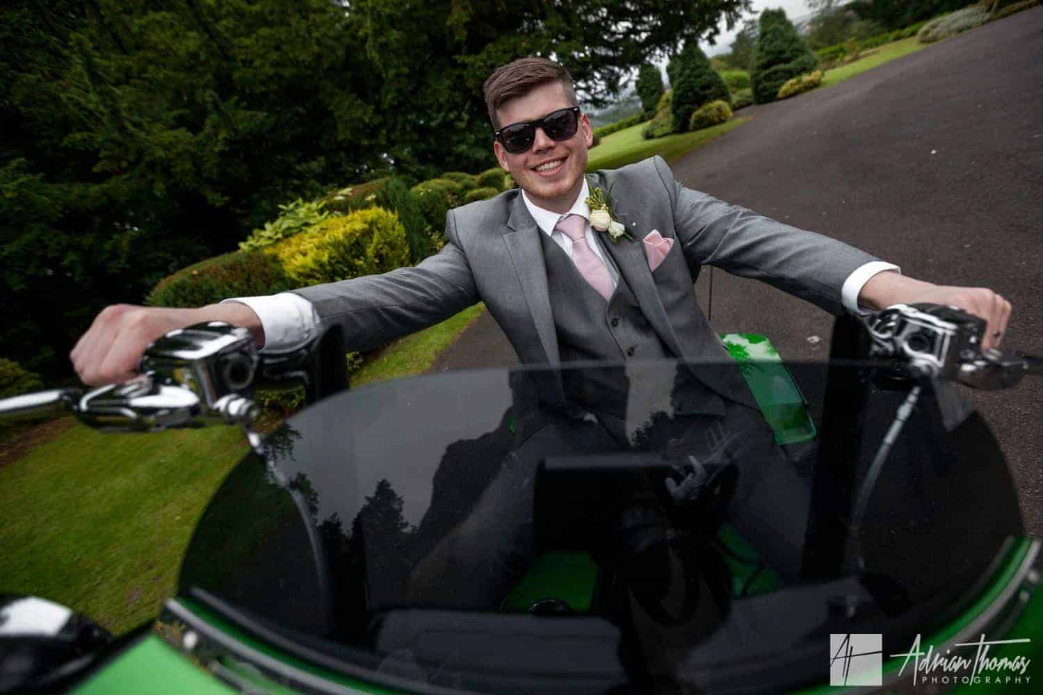 Groom sitting on a motor bike.