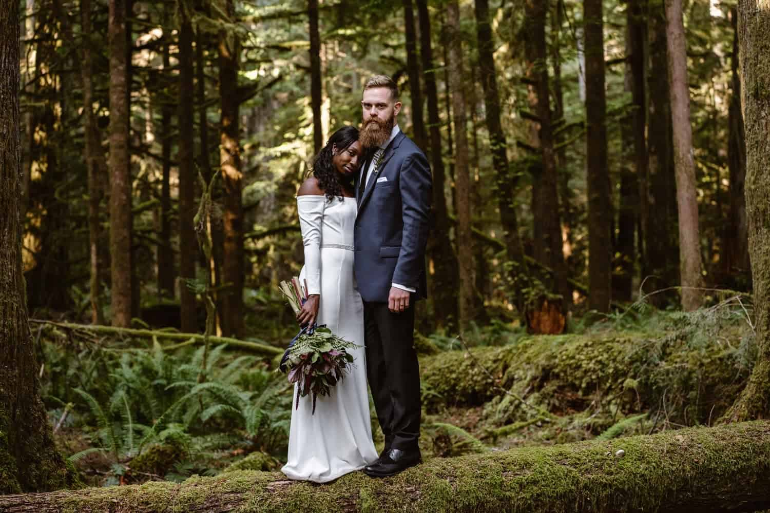Bride and Groom hiking in forest at  Olympic National Park Elopement
