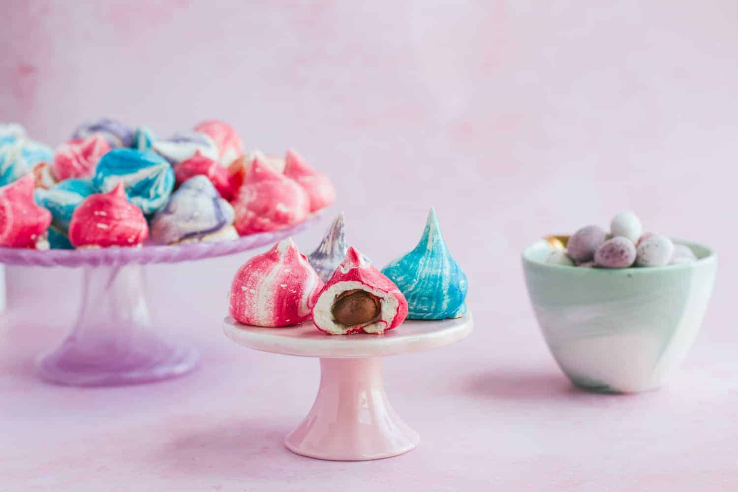 Cake stands with mini meringues in blue, pink and purple