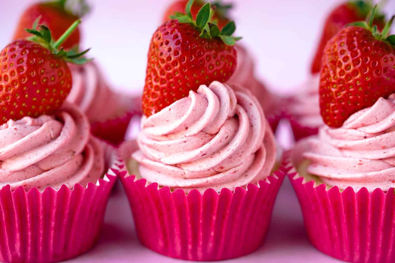 A row of pink strawberry cupcakes in pink cases topped with fresh strawberries