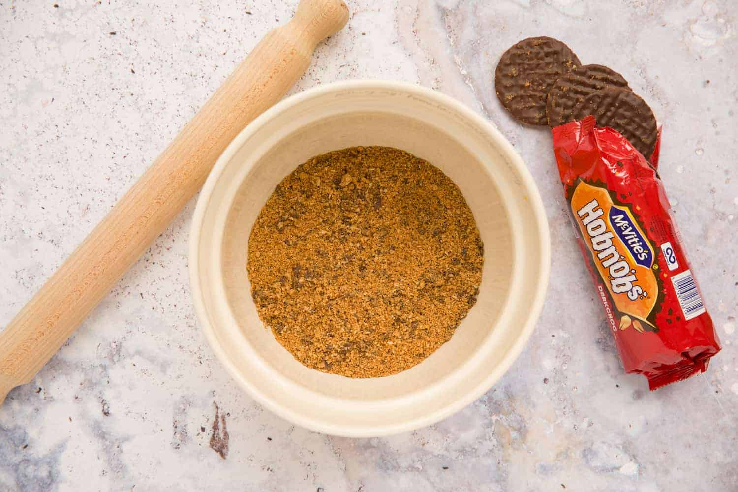 Overhead shot of a mixing bowl filled with crushed Hobnob biscuits. There is a rolling pin to the left of the bowl and a packet of chocolate Hobnob biscuits to the right of the bowl.