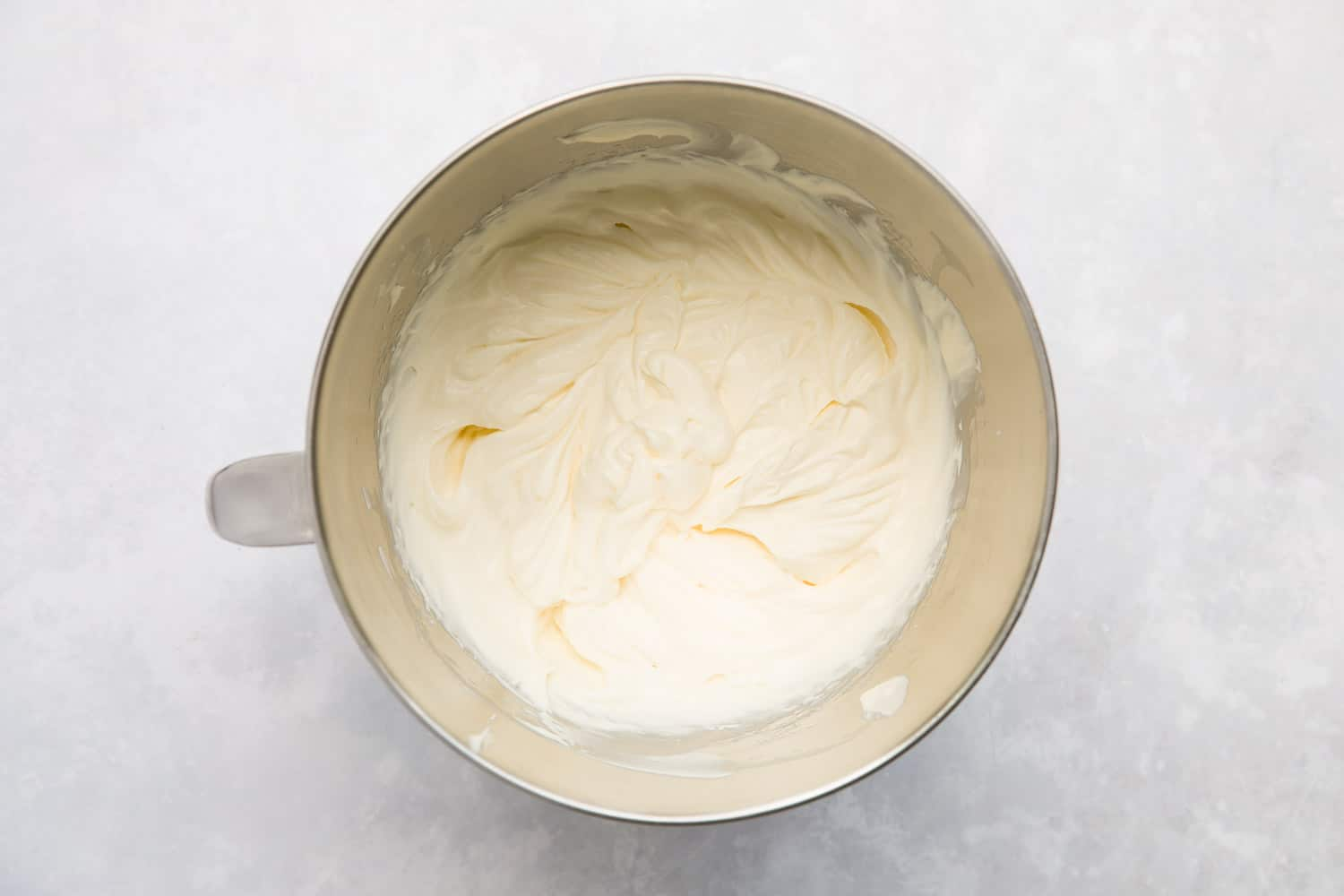 A mixing bowl containing whipped double cream and condensed milk.