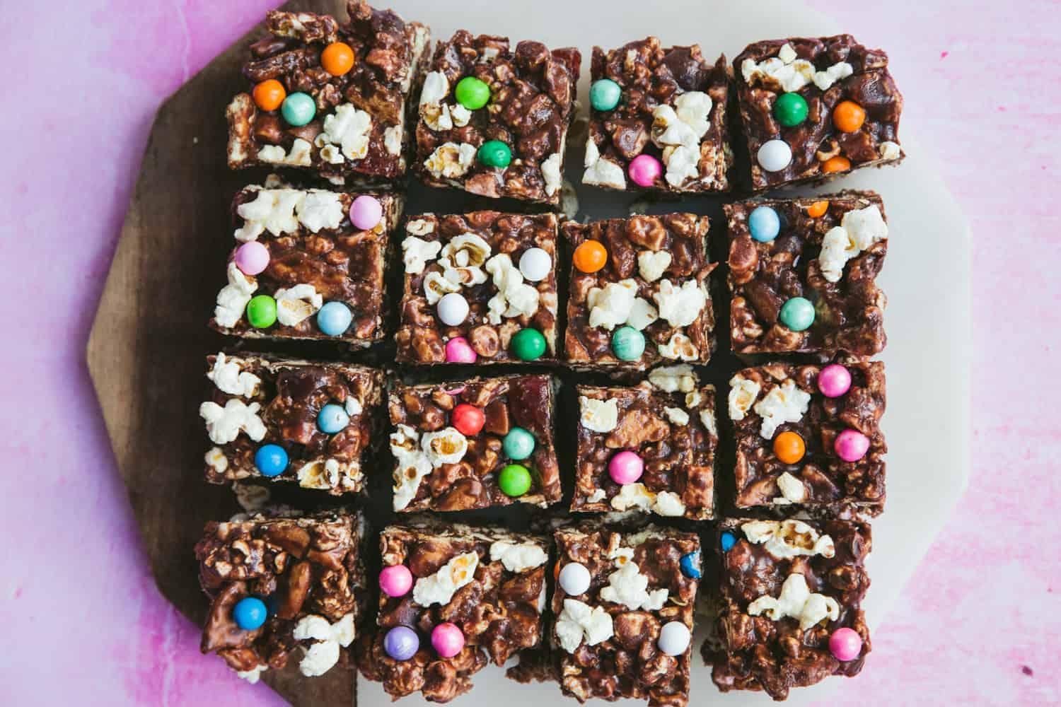 16 squares of Popcorn Rocky road on a pink background.