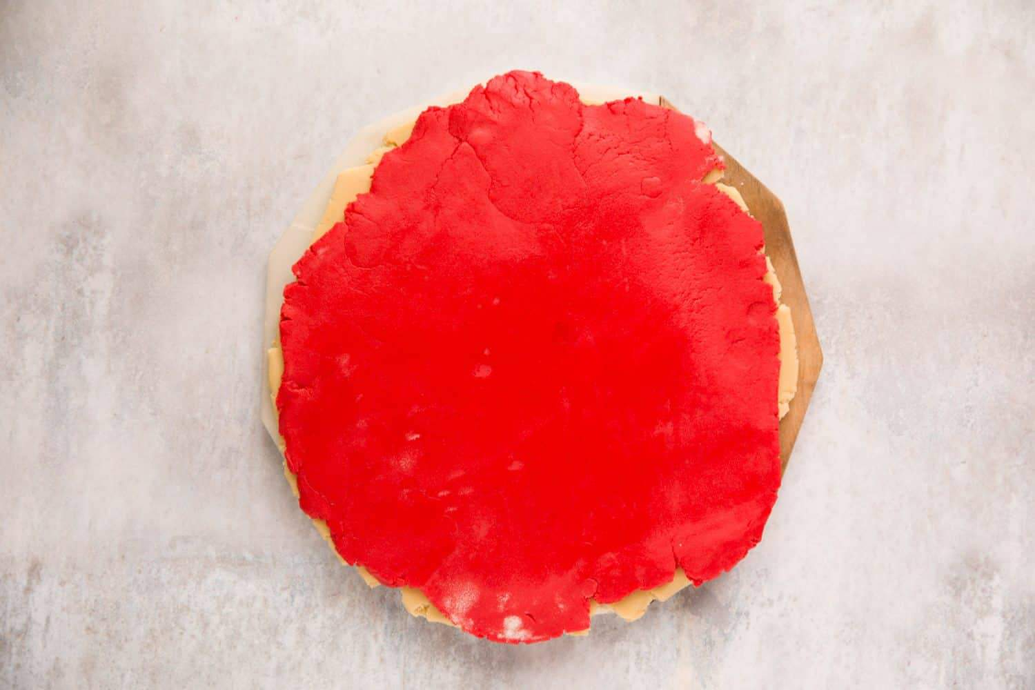 A sheet of red coloured vanilla biscuit dough.