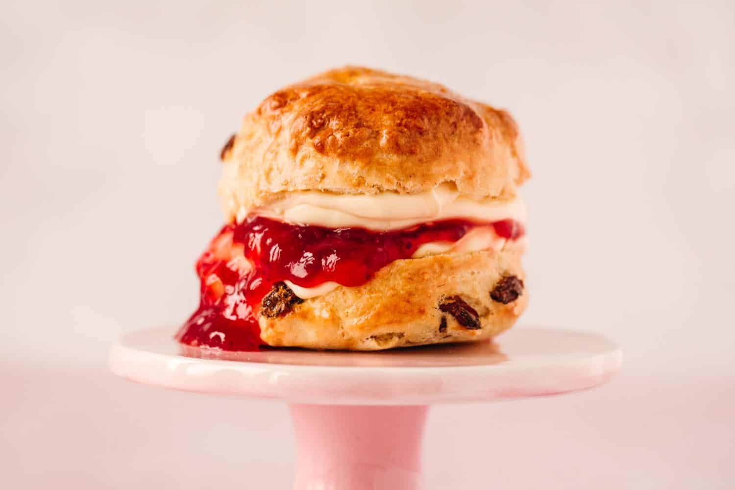 Profile image of a scone on a pink cake stand with a pale pink background.