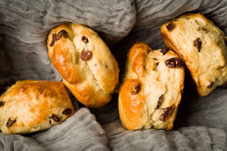 Overhead image of 4 scones lying on top of a dark grey piece of linen.