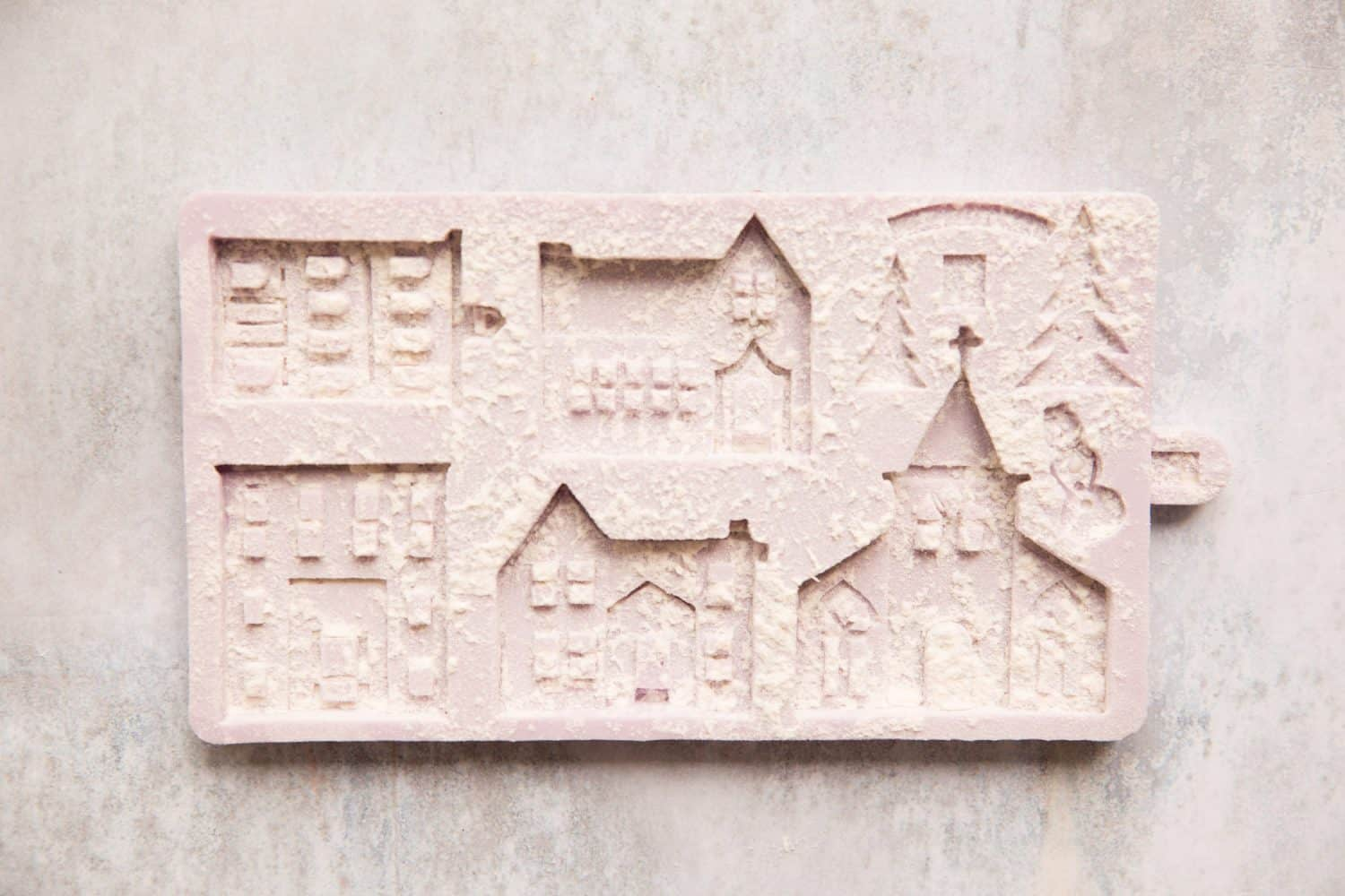 A gingerbread house mould that has been dusted with flour.