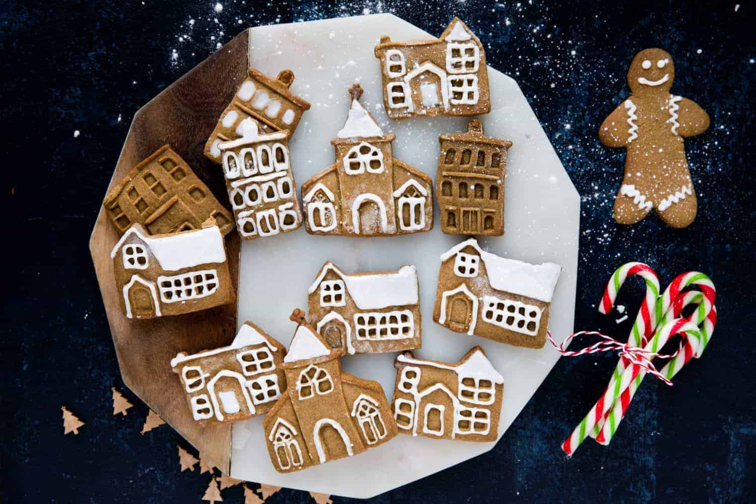 Gingerbread houses, churches and a gingerbread man on a dark blue background.