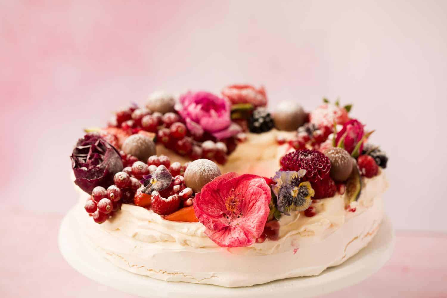 ¾ angle of a circular pavlova that has been decorated with fruit and edible flowers.