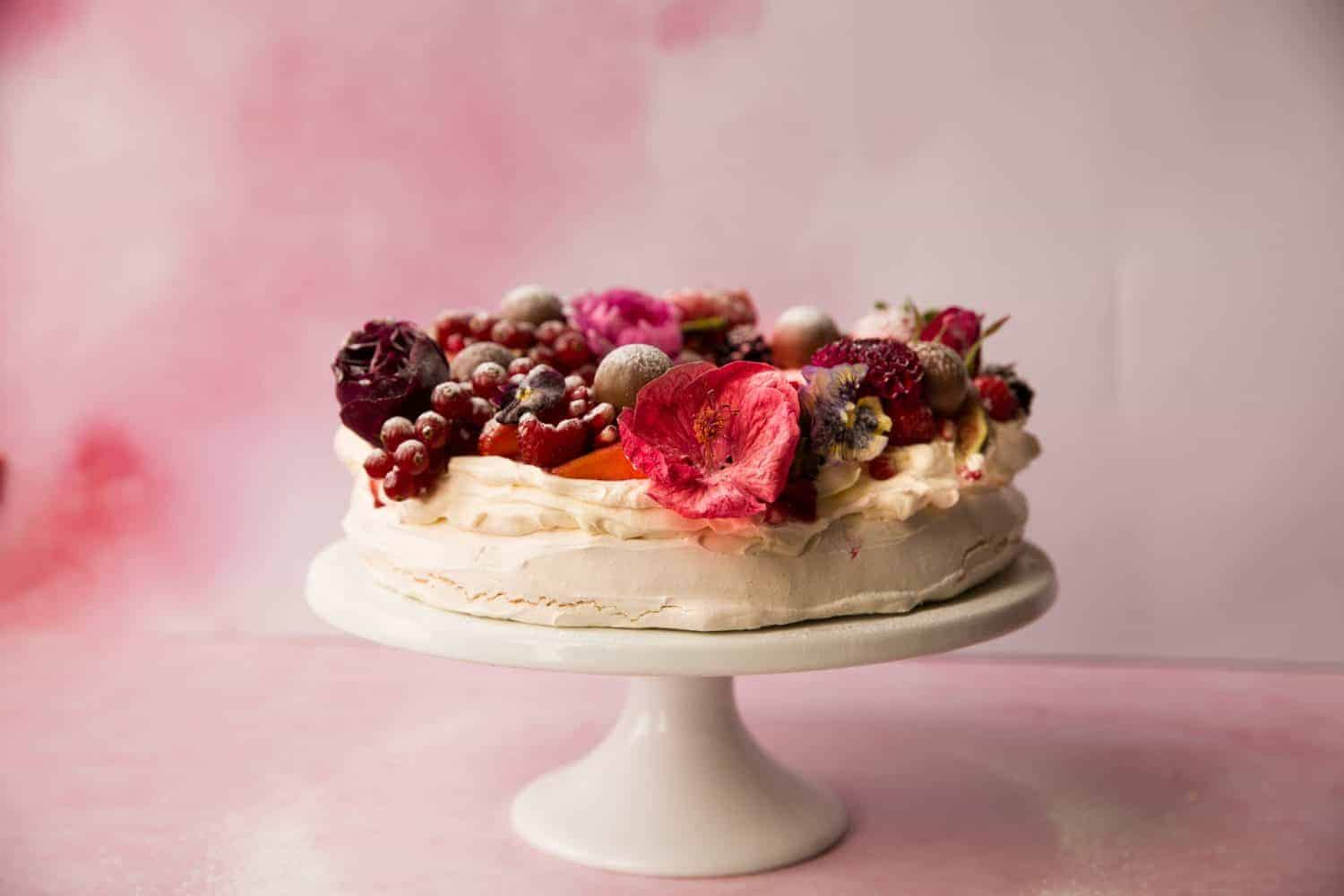 Pink background with a  pavlova dessert on a white cake stand.