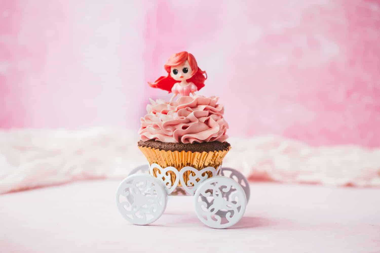 An Ariel cupcake on a white chariot cupcake holder.