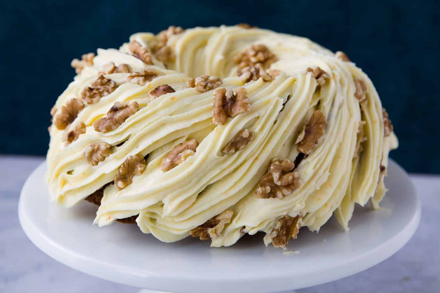 A carrot cake bundt on a white cake stand. There is frosting all over the cake and whole walnuts have been added for decoration.