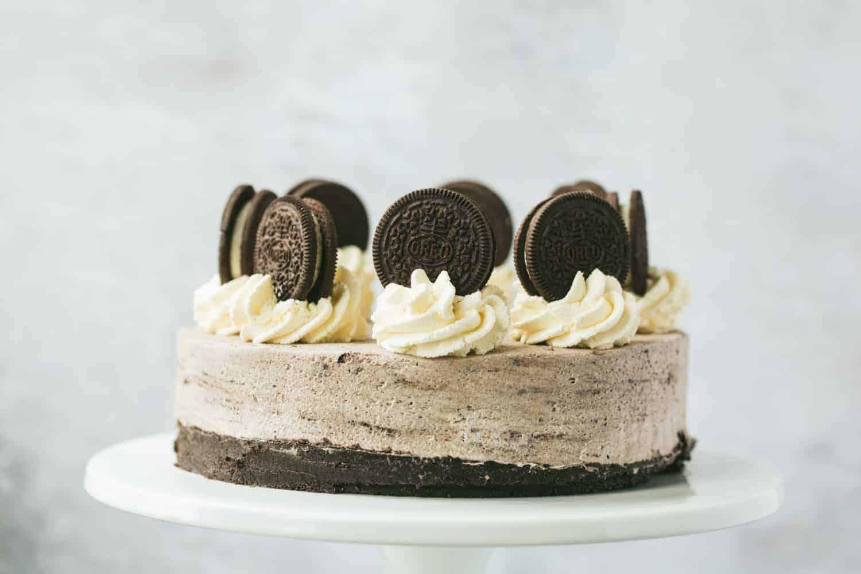An Oreo Cheesecake on a white cake stand.