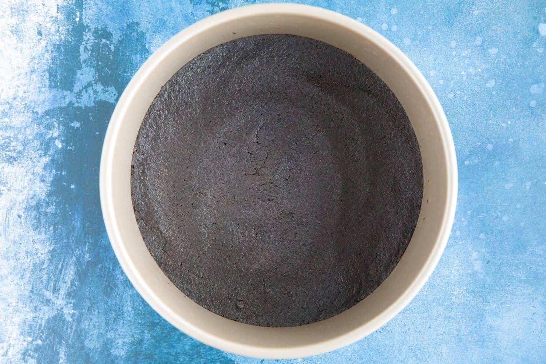 Oreo cheesecake crust in a baking tin.