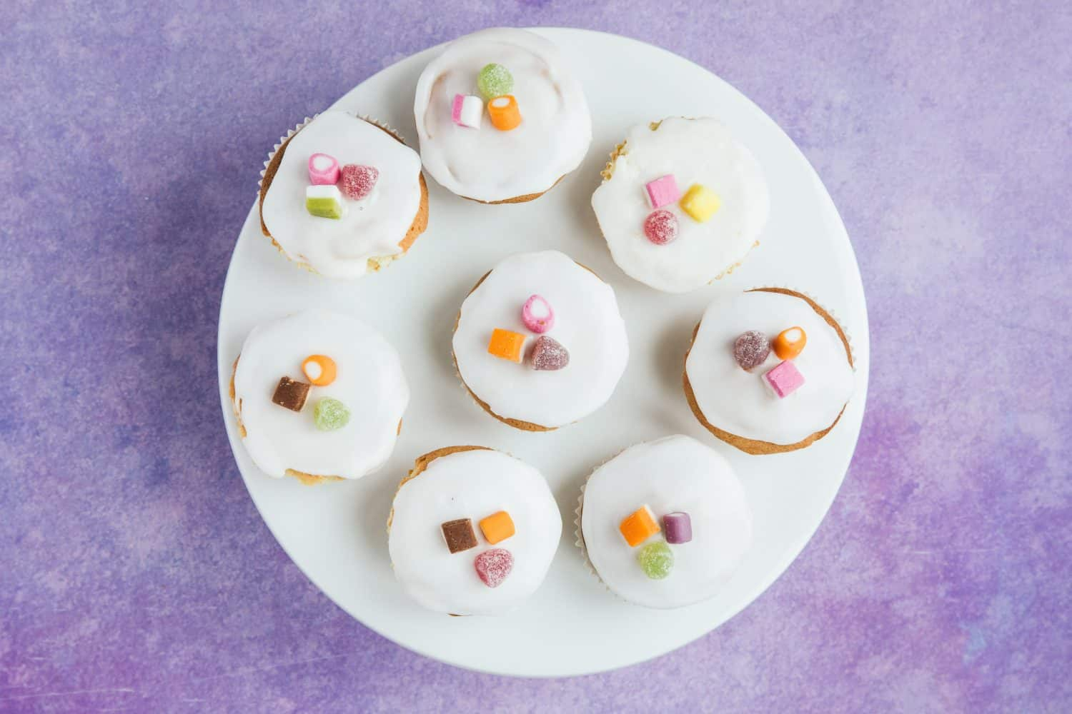 A white cake stand with 8 fairy cakes on top.