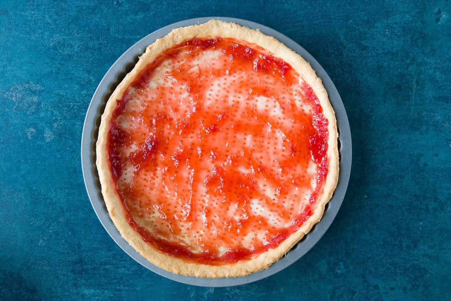 Strawberry jam spread over the top of cooked shortcrust pastry.