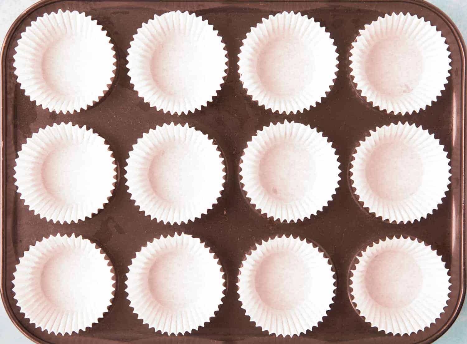 A 12 hole cupcake tray lined with 12 white cupcake cases