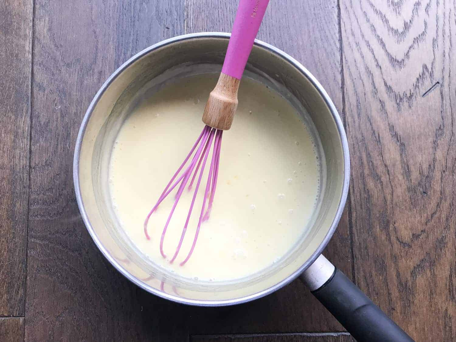 A saucepan with cream, sugar, lemon zest and lemon juice with a whisk inside