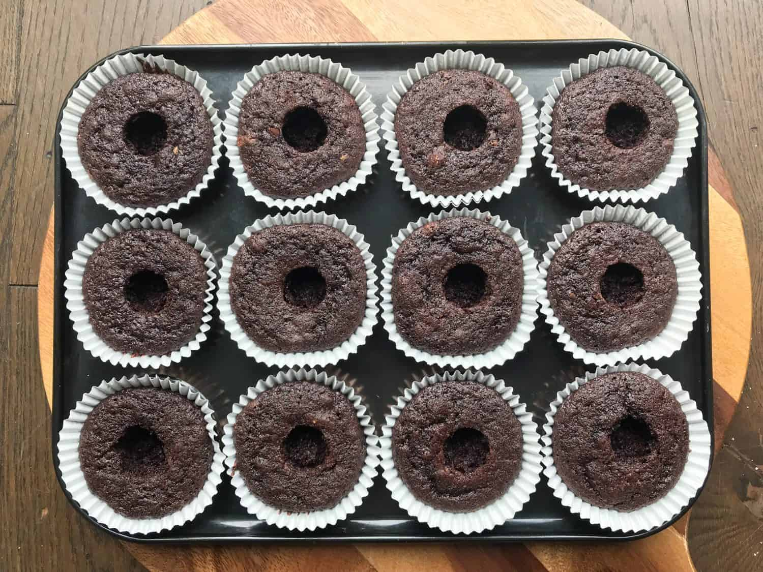 A tray of 12 chocolate cupcakes with holes in the centre.