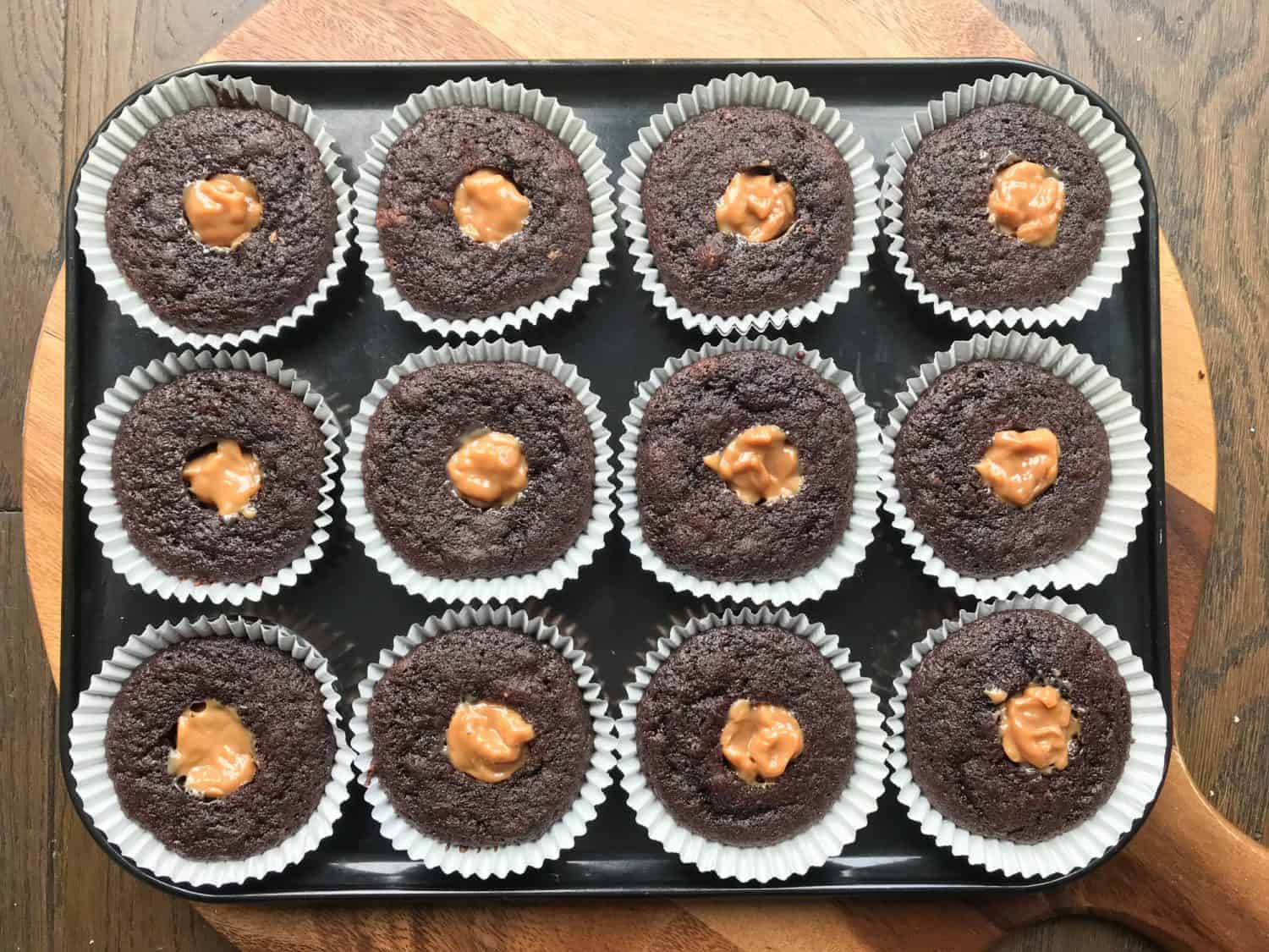 A tray of 12 chocolate cupcakes with holes in the centre. Each hole has been filled with caramel sauce.