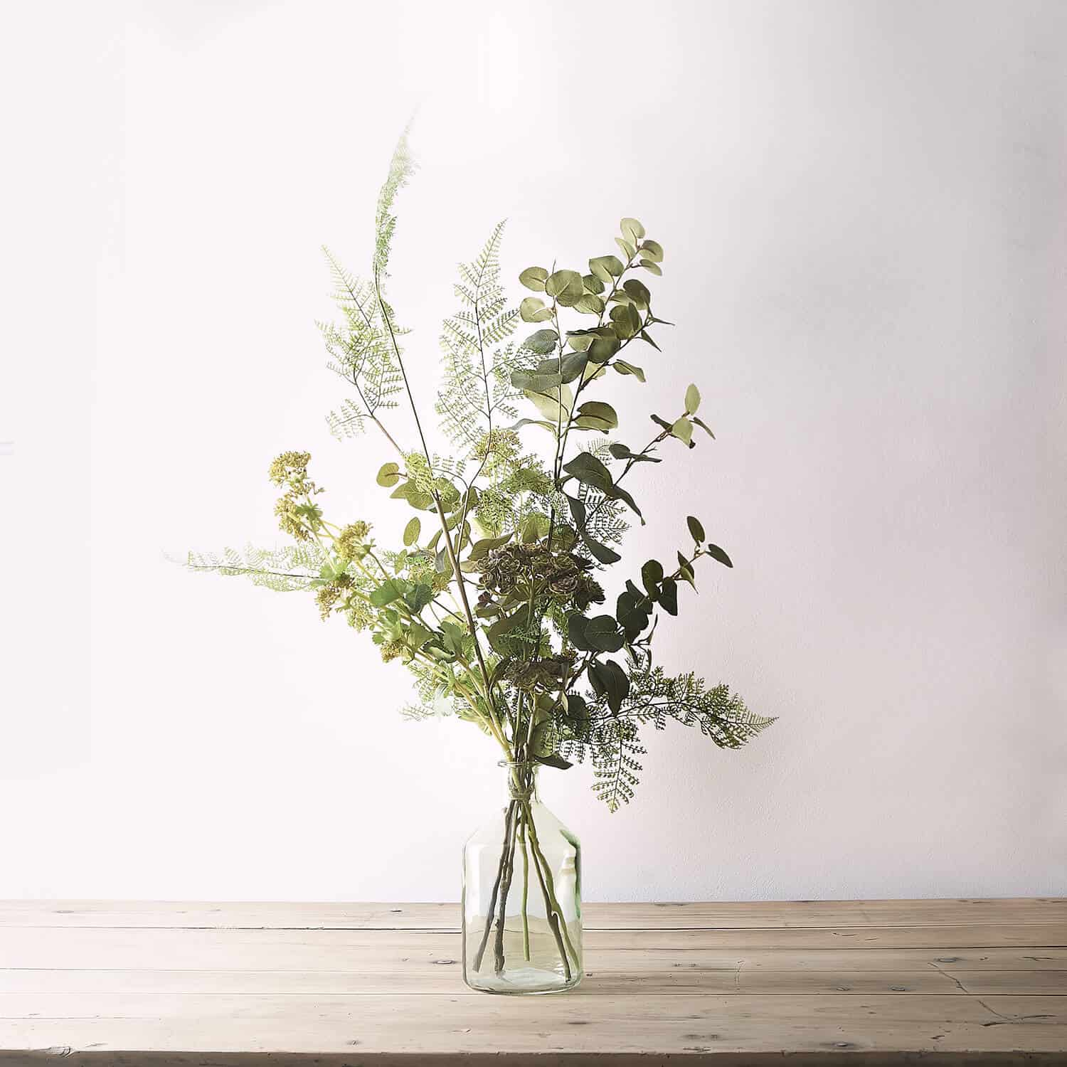 Artificial flower arrangement photographed in the studio with diffused lighting on rustic industrial surface