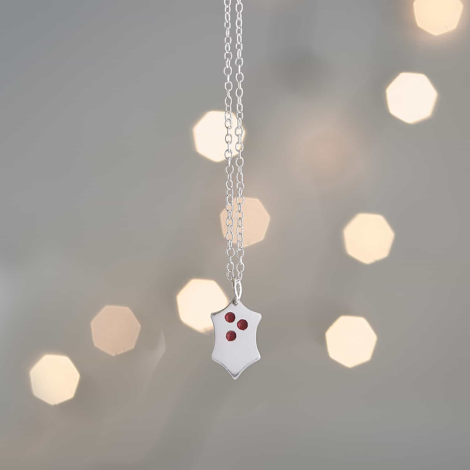 Silver pendant product photograph with lights in the background out of focus bokeh