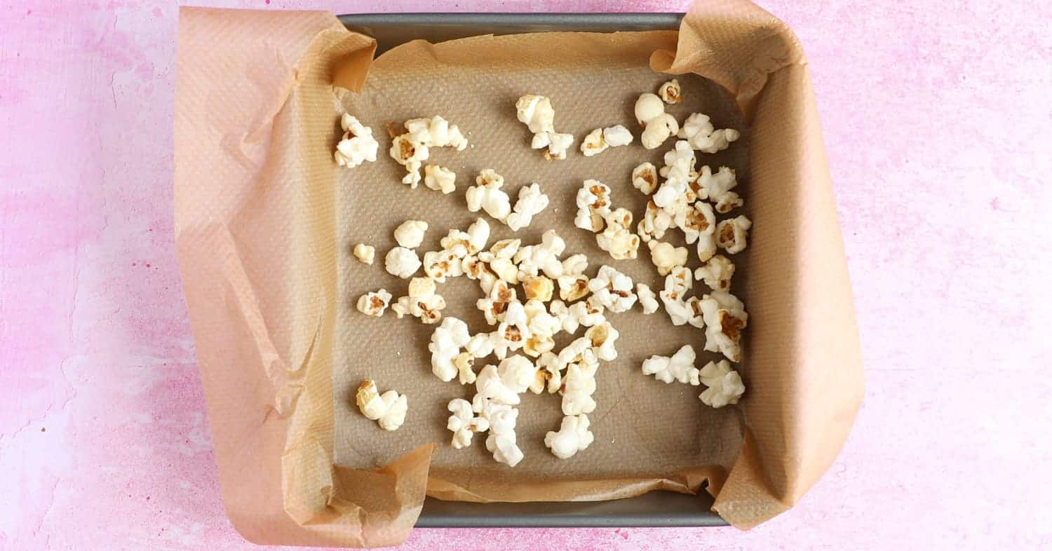 A layer of popcorn in a square baking tin.
