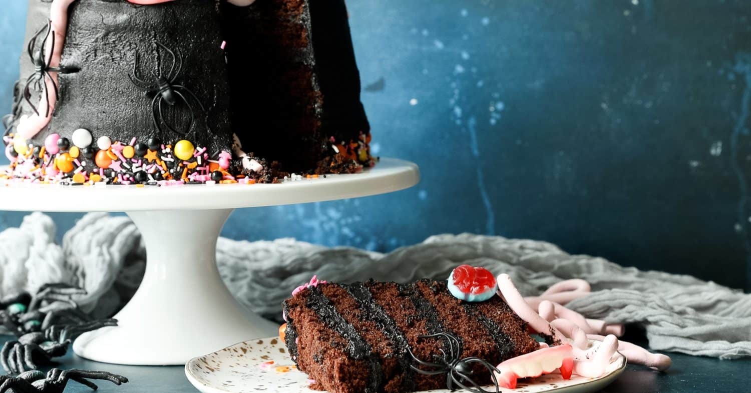 A slice of cake on a plate. In the background is a black Halloween cake covered in sweets.