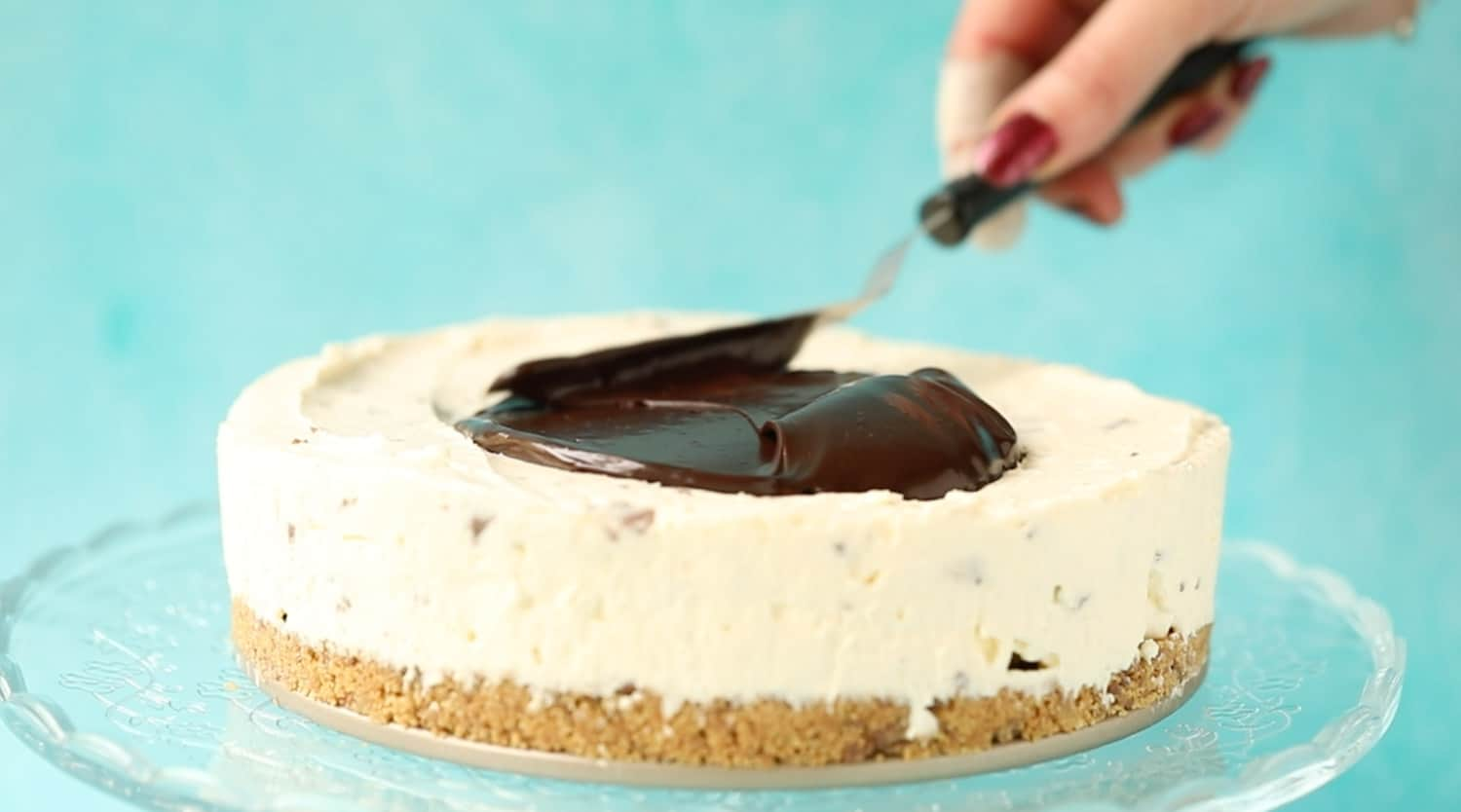 Spreading a cheesecake with chocolate ganache