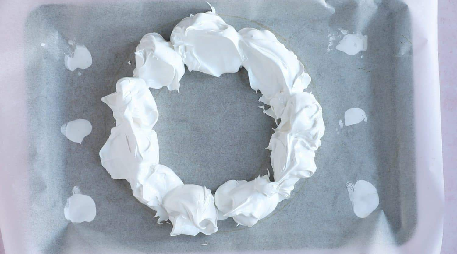 Adding meringue mixture in a wreath shape on to a baking tray.
