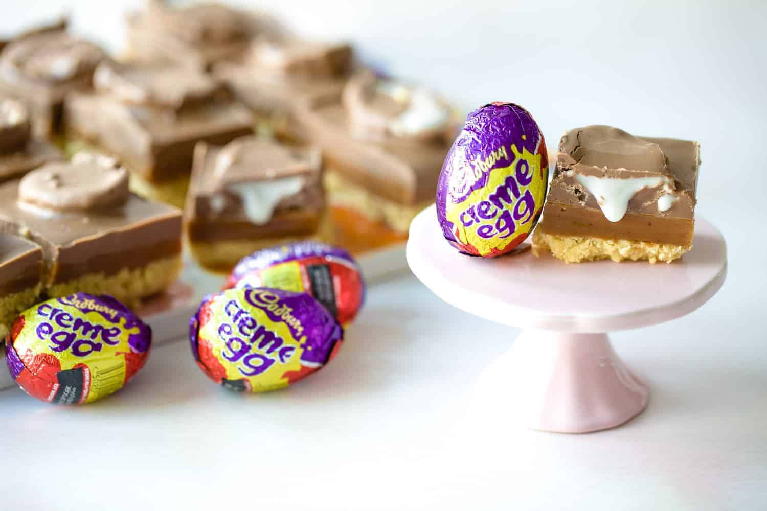 A slice of Creme Egg Shortbread with a Creme Egg beside it