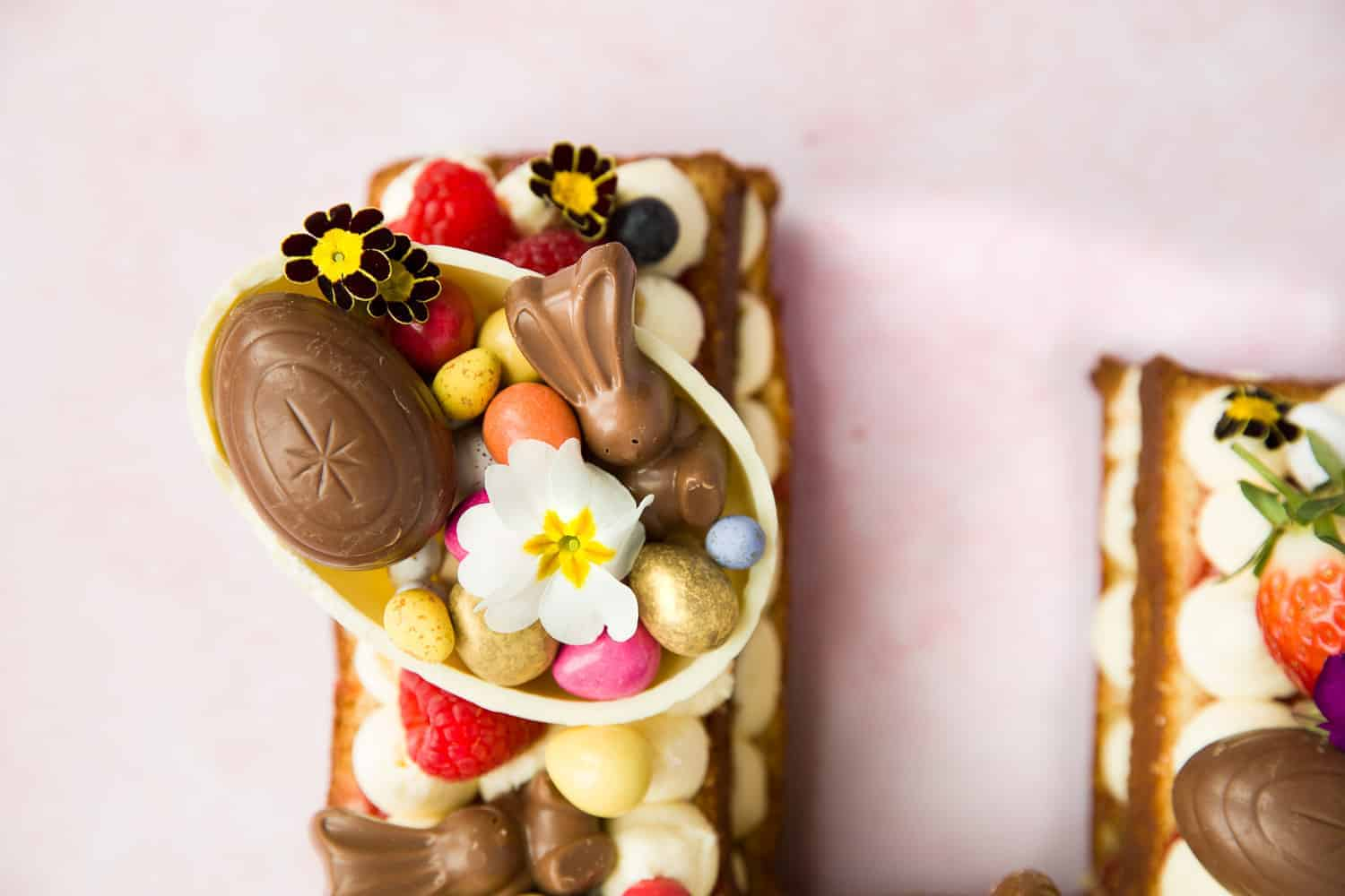 A cake topped with half a white chocolate easter egg