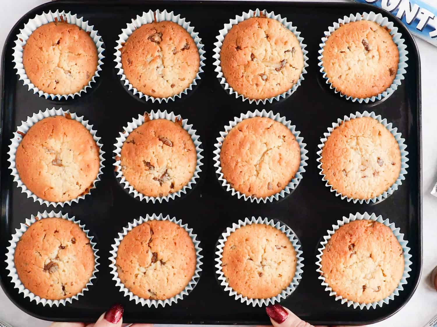 A baking tray filled with 12 cupcakes that have just come out of the oven