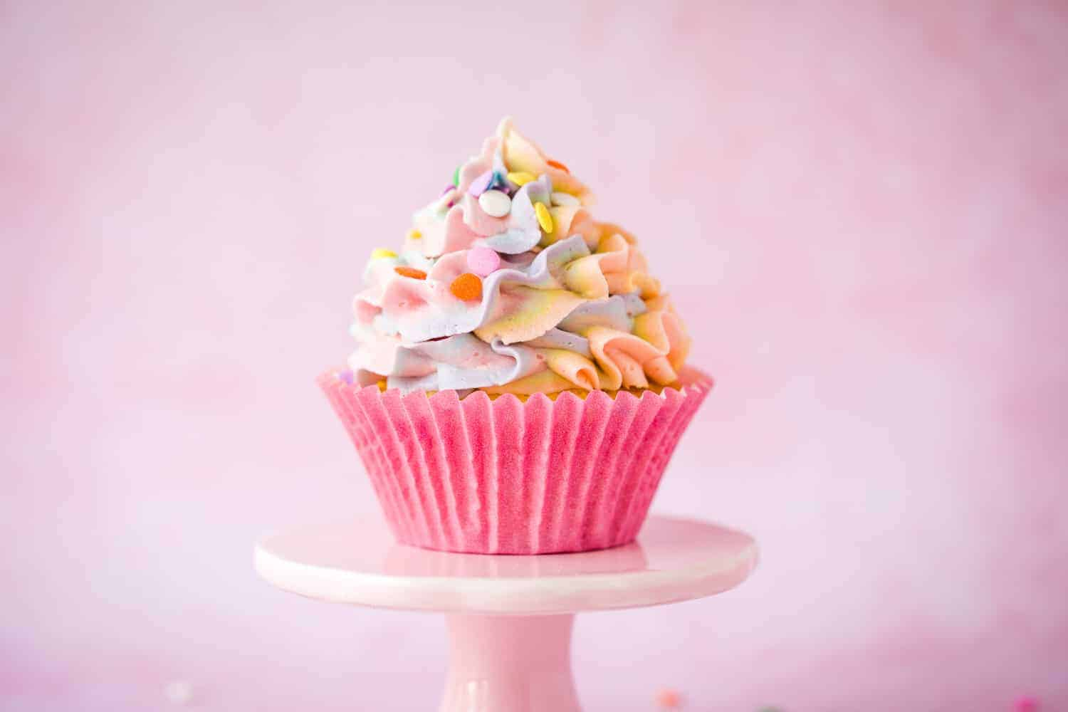 A piñata cupcake on a small pink cake stand with ruffle rainbow coloured icing