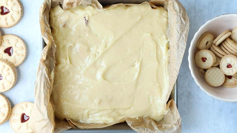 Jammie Dodger blondie mixture in a square baking tin.