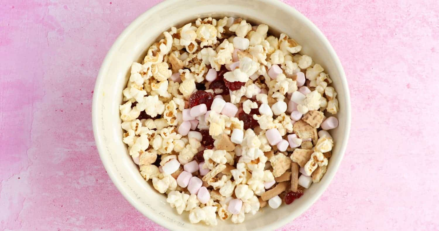 A mixing bowl with rich tea biscuits, mini marshmallows, glace cherries and popcorn