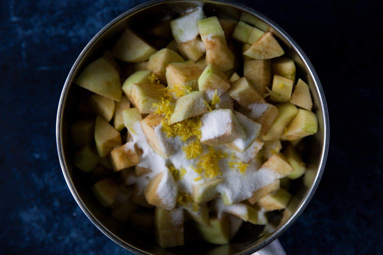 A saucepan containing apples, sugar and lemon zest.